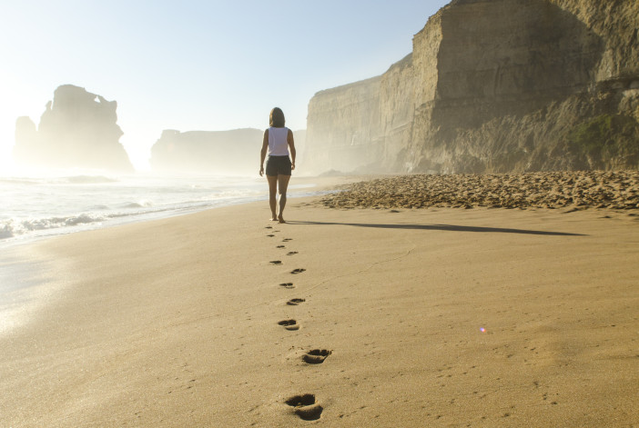 Woman walking in sand footprints in sand