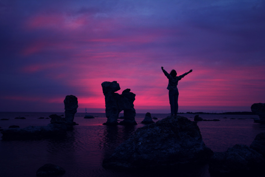 Woman on rocks hands open at sunset